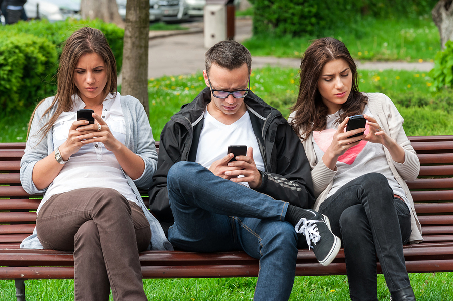 Group of friends two women and one man, sitting on a bench in park separately looking at their phones loosing communication. people using their phones and sending texts as they stand beside each other ** Note: Soft Focus at 100%, best at smaller sizes